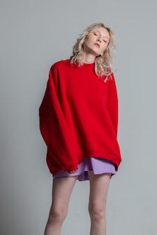 白い背景の上の赤い長いスウェットシャツでポーズをとってかなり若いファッショニスタ