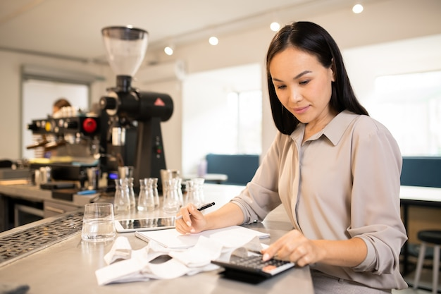 Pretty young female accountant of modern cafeteria or restaurant counting total sum of receipts at the end of working day