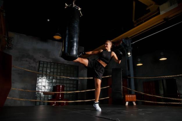 スポーツ ボクシングのリングでかなり若い女性ボクサーが古いジムでサンドバッグを蹴る