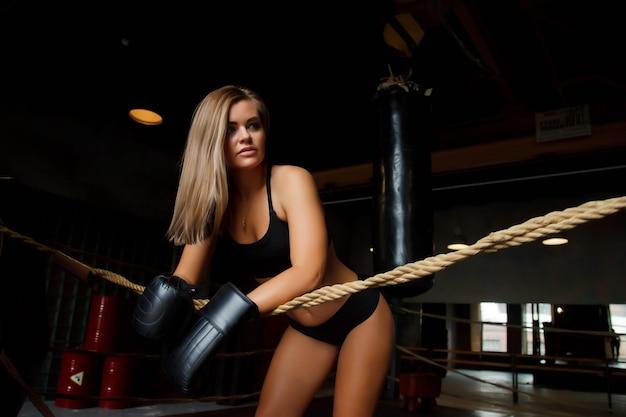 かなり若い女性のボクサーは、ボクシンググローブをはめて、古いジムのロープでリングに立っています。ボックストレーニングの女性。健康的なライフスタイル、スポーツ、ジムでの運動の概念。コピースペース