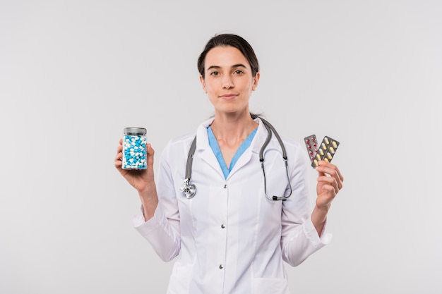 Pretty young female clinician in whitecoat holding jar with pills and blisters with painkillers in isolation