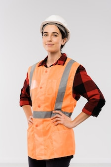 Довольно молодая женщина-инженер в шлеме и оранжевой куртке держит руки на талии, стоя перед камерой
