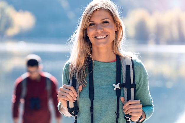 Довольно молодая женщина турист улыбается, глядя на камеру перед озером.