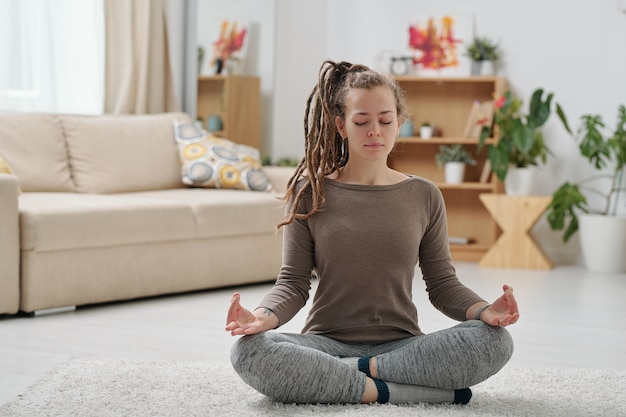 Довольно молодая женщина в спортивной одежде сидит на полу со скрещенными ногами во время расслабляющих упражнений йоги