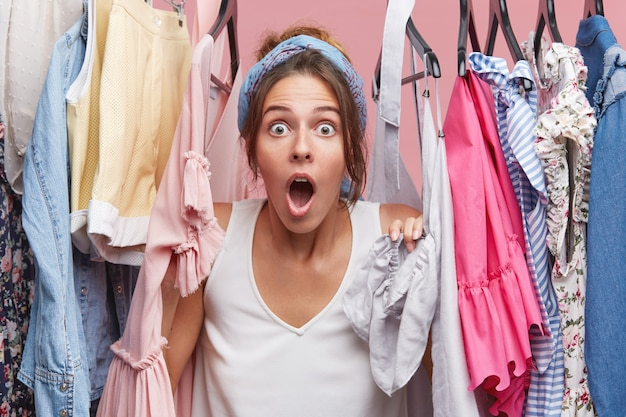 Pretty young female looking with bated breath, posing near hangers with clothes, being shocked to realize that her favourite dress is dirty. people, emotions, body language concept