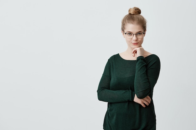 Pretty young female looks with appeal  having her blonde hair tied in knot wearing big glasses and green loose sweater holding hand under her chin, building plans, thinking about something