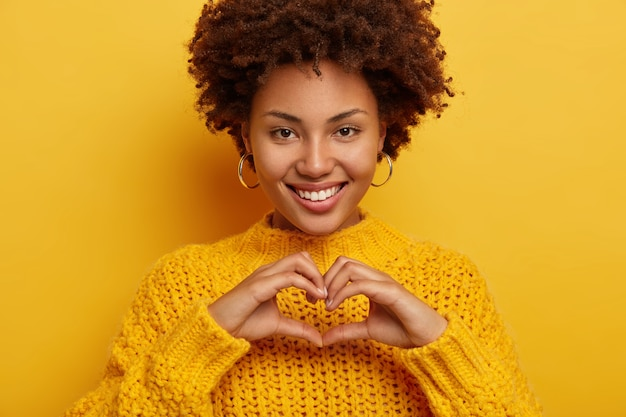 かなり若い女性は、愛のしぐさを作り、真実の気持ちを告白して表現し、広く笑顔を見せ、白い歯を見せ、黄色いセーターを着て、優しい表情をしています