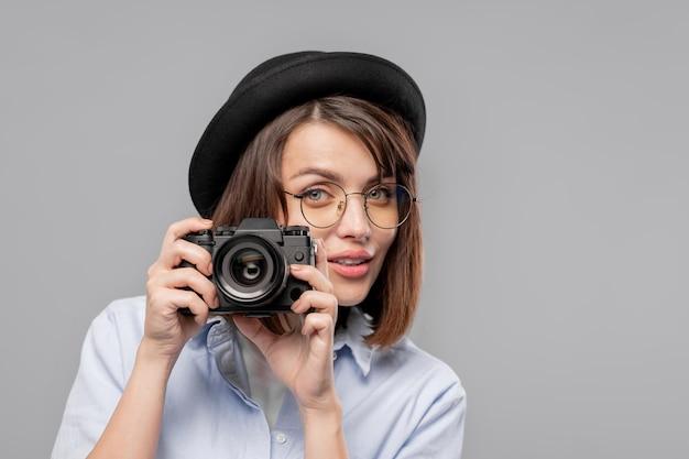 Довольно молодая женщина-фотограф с камерой, глядя на вас, собираясь сделать снимок