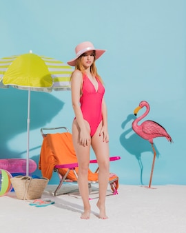 Pretty young female posing in hat and swimsuit in studio