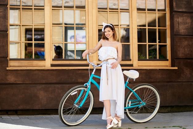 카페의 큰 슬라이딩 창문이있는 건물 앞에서 청록색 자전거 옆에 포즈를 취하는 꽤 젊은 여성