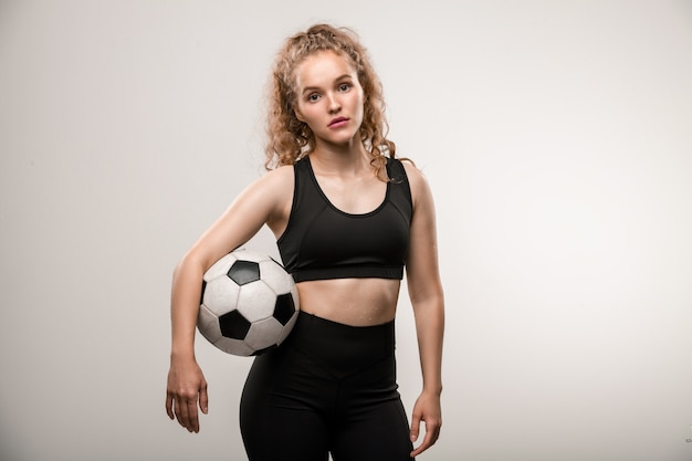 Pretty young female soccer player with long blond curly hair holding ball between arm and waist