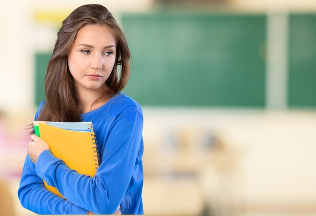 Pretty young female student on background