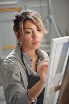 Довольно молодая студентка в фартуке сидит перед мольбертом, работая над незаконченной картиной на уроке в школе искусств