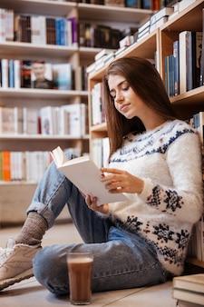 Довольно молодая студентка читает книгу на этаже библиотеки в университете