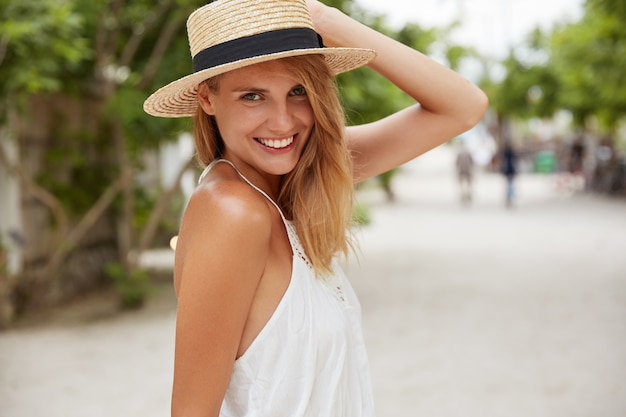 Pretty young female in summer hat and white dress, has positive expression, poses outdoor on coastline in tropical place, enjoys hot weather and sunshine. people, rest, lifestyle, season concept