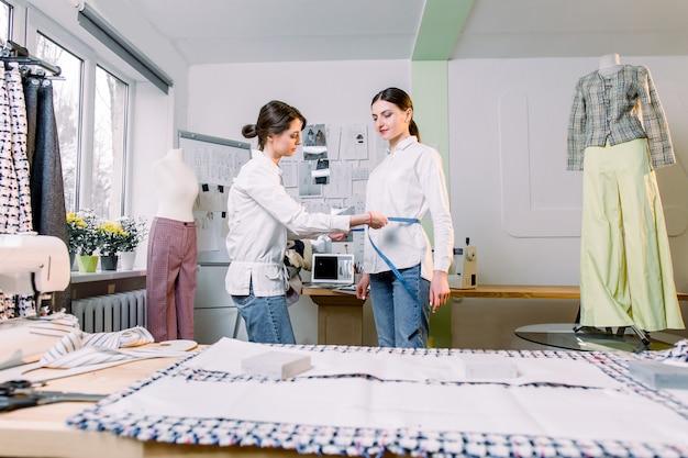 Довольно молодой женский портной измерения ее клиента женщина, чтобы сделать стильную одежду в своей студии портниха. швейная промышленность, пошив одежды, концепция ателье по пошиву одежды