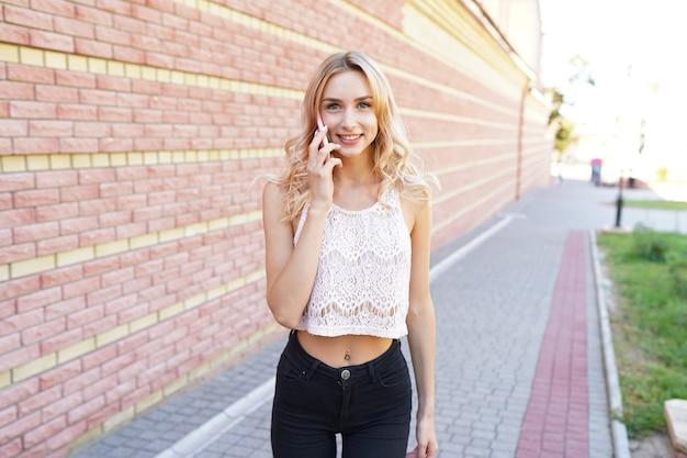 笑顔で白い携帯電話を使用してかなり若い女性
