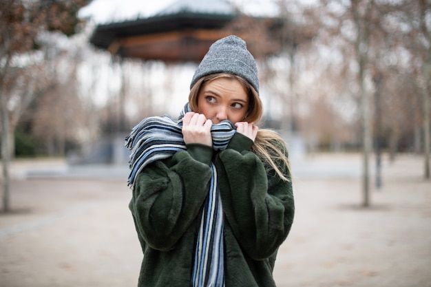 Pretty young female in warm clothes wrapping in scarf and looking away in autumn park on really cold day