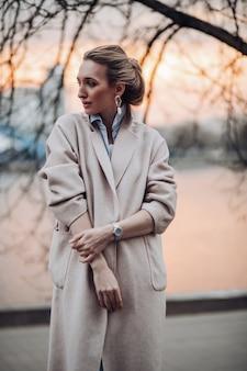 秋の服、暖かい居心地の良いコートを着て、日没時に屋外でポーズをとるかなり若い女性。自然な女性の美しさ