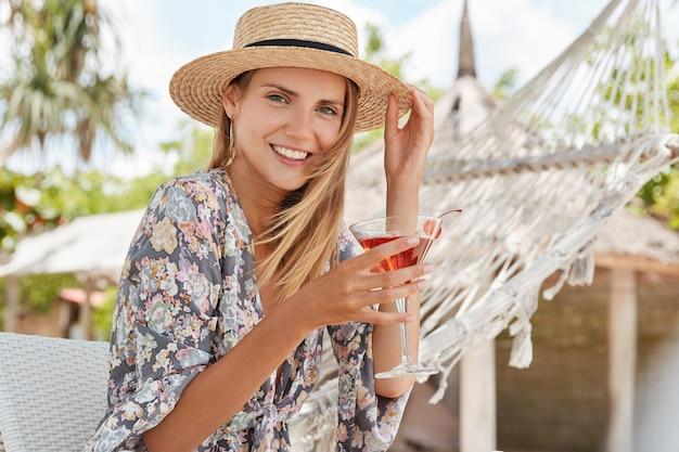 Piuttosto giovane donna indossa un cappello estivo, tiene un bicchiere di cocktail, ha un'espressione felice e un aspetto piacevole, si siede contro un'amaca su una sedia all'aperto, respira aria fresca e gode di un clima soleggiato. tempo di riposo