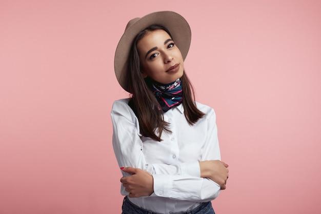 핑크 스튜디오 벽에 고립 된 교차 손으로 꽤 젊은 여성