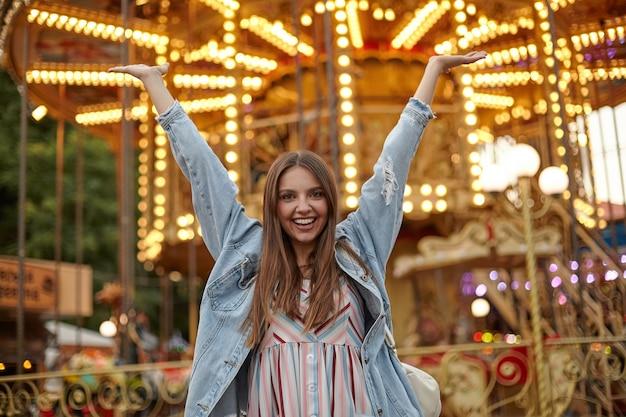 Bella giovane femmina con lunghi capelli castani guardando con un sorriso sincero e alzando la mano felicemente, indossando un abito romantico e cappotto di jeans
