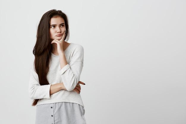 Довольно молодая женщина с длинными темными волосами, глядя прочь, держа руку под подбородком, строить планы, думать о чем-то. задумчивая брюнетка красивая женщина с задумчивым и задумчивым выражением лица