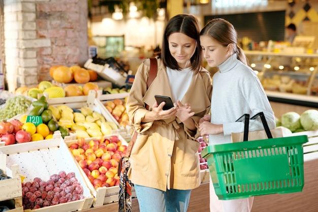 Довольно молодая женщина со смартфоном и ее дочь с корзиной