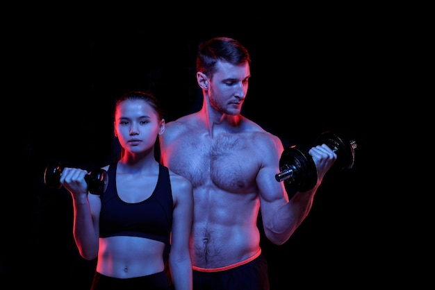 Довольно молодая подтянутая женщина и мускулистый спортсмен без рубашки с гантелями тренируются вместе