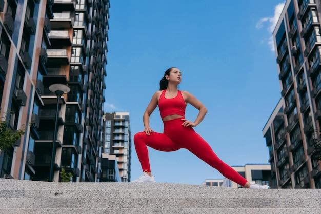 赤いスポーツトップとレギンス、階段でストレッチ運動をしている白いスニーカーのかなり若いフィットの女性