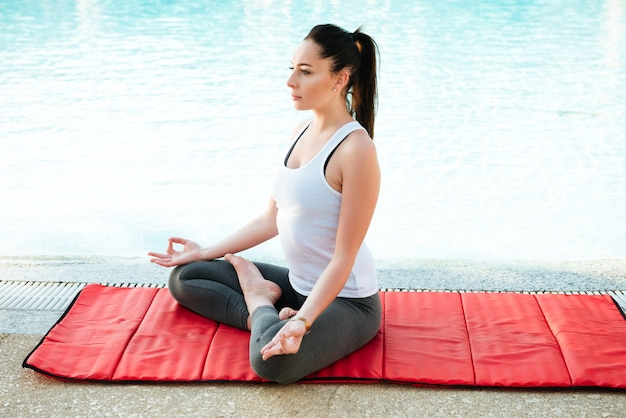 Pretty young fitness lady make yoga exercises near pool.