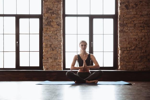 Довольно молодая фитнес-леди делает упражнения йоги.