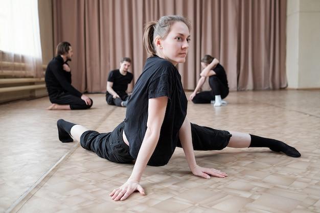 Довольно молодая гибкая танцовщица в черной спортивной одежде тренируется на полу в студии современного танца во время тренировки
