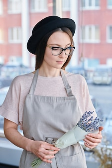 Pretty young floral shop assistant in hat, eyeglasses and apron holding bunch of lavender wrapped in paper