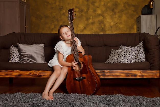 기타 방 내부에 소파에 앉아 꽤 젊은 4 살짜리 소녀. 집에서 행복 한 아이
