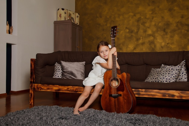 Pretty young four-year-old girl with guitar sitting on sofa in interior of room. happy child at home. concept of house learning or playing guitar at home. copyright space for site or banner