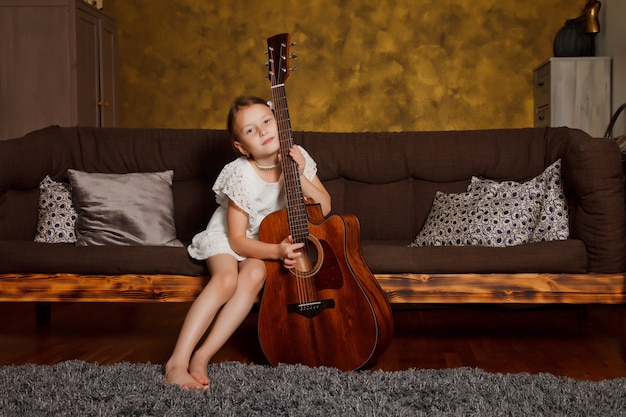 Pretty young four-year-old girl with guitar sitting on sofa in interior of room. happy child at home