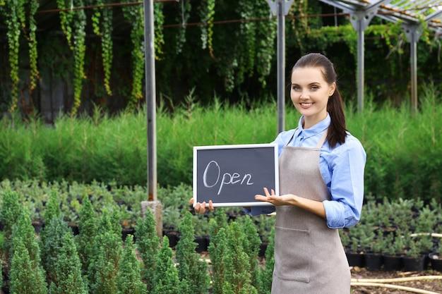 Openの碑文が付いているかなり若い庭師の保持板
