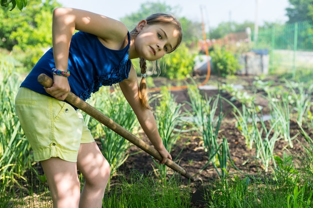 鍬で新鮮な新しい植物の間の除草の上に曲がる野菜パッチで働いているかなり若い庭師