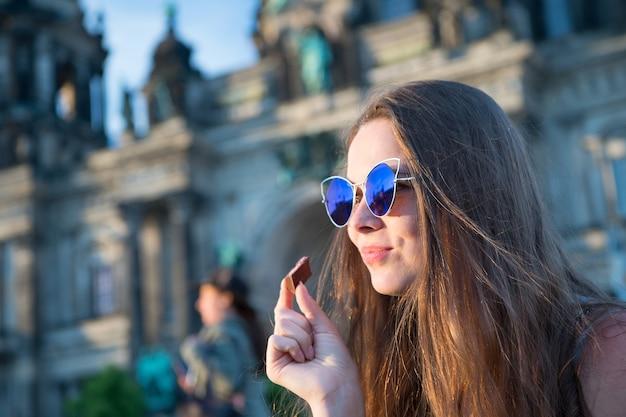 아름다운 석양에 베를린 대성당 앞에 앉아 초콜릿을 먹는 예쁜 어린 길