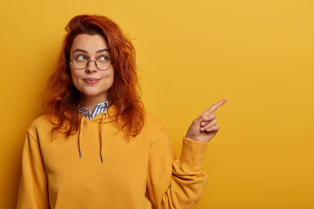Pretty young ginger girl points index finger on left at blank space, advertises something, wears optical glasses and yellow sweatshirt
