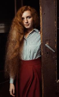 緑豊かな赤い髪とそばかすが古いドアに立っているかなり若い生姜の女性