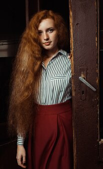 Pretty young ginger woman with lush red hair and freckles standing at the old doors