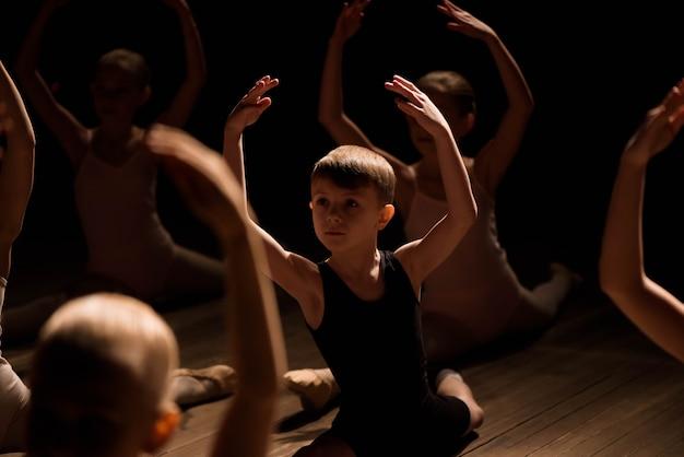 꽤 어린 소녀와 소년 스트레칭과 발레 댄스 훈련 무대에 앉아.