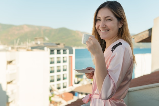 Pretty young girl in bathrobe drinking coffee while standing on the balcony of her room at the hotel and looking at camera