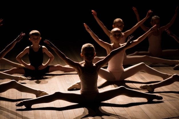 Pretty young girl and boy sitting on stage having stretching and training for ballet dances.