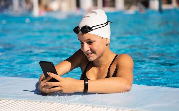 Ragazza abbastanza giovane che passa in rassegna il telefono cellulare alla piscina