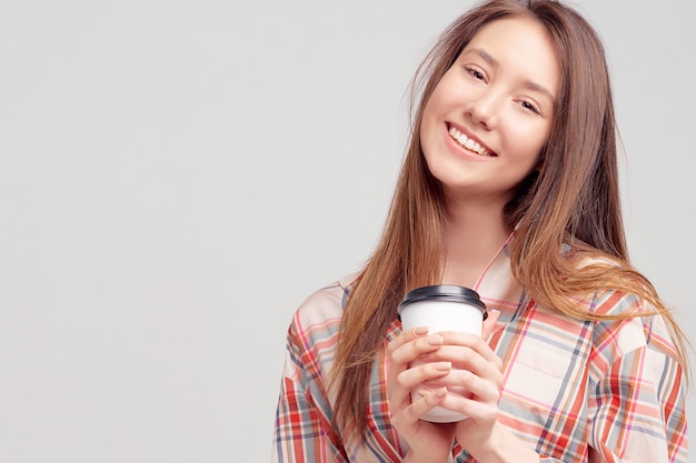 A pretty young girl, in casual clothes, smiles sweetly and holds a glass of coffee in a disposable package.