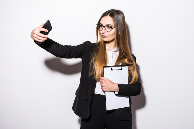 Pretty young girl dressed up in black modern suite makes selfie on her phone on white