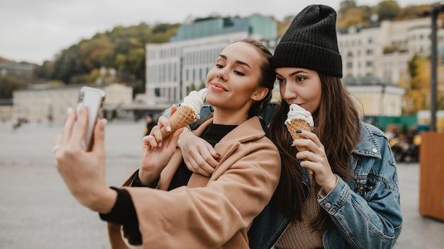 Довольно молодая девушка вместе наслаждаясь мороженым